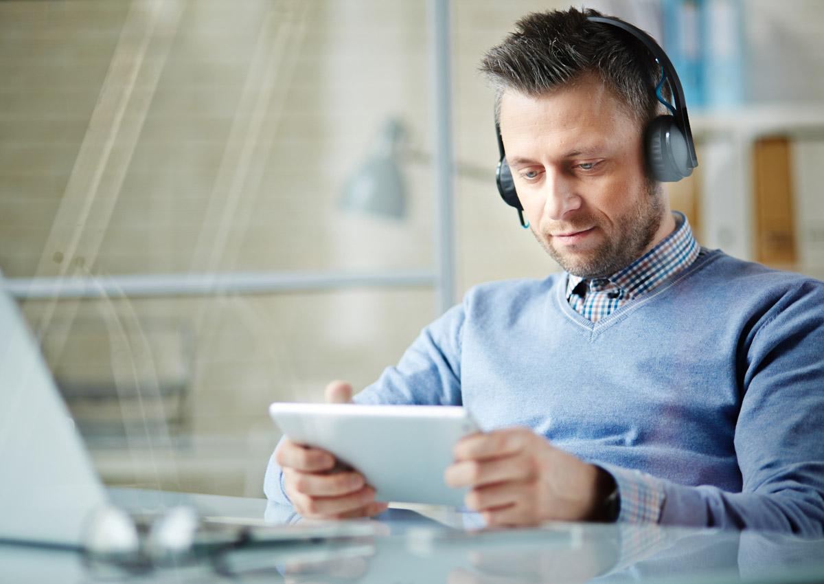 Mann mit Kopfhörern schaut sich etwas auf dem Tablet an.